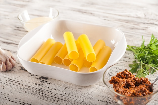 Процесс изготовления макарон. сырцовые макароны cannelloni на светлом конце-вверх таблицы и космосе экземпляра.