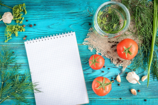 缶詰のトマト。青い木製の背景の保存のためのディル、ニンニク、スパイスとハーブで調理した新鮮なトマト。