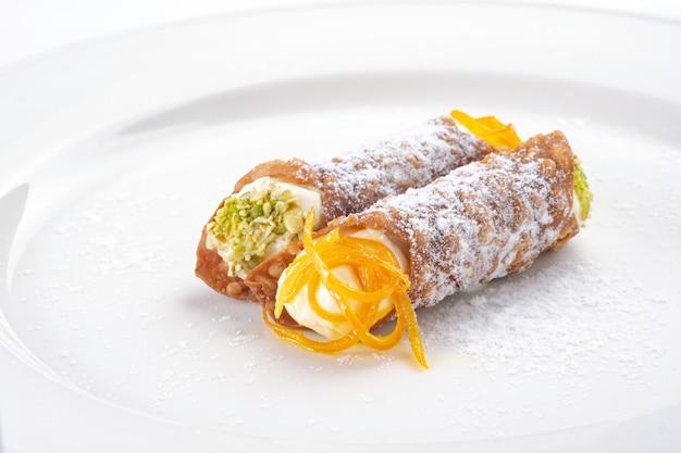 하얀 접시에 리코타 치즈와 피스타치오를 곁들인 카놀리 달콤한 시칠리아 디저트
