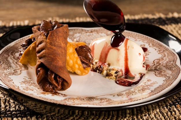 Cannoli with ice cream, chocolate and almonds in the plate