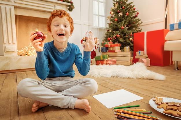 幸せになることはできません。興奮した赤毛の子供のローアングルショットは、床に座ってクリスマス休暇を最大限に楽しんでいる間、彼の感情を中に保つことができません。