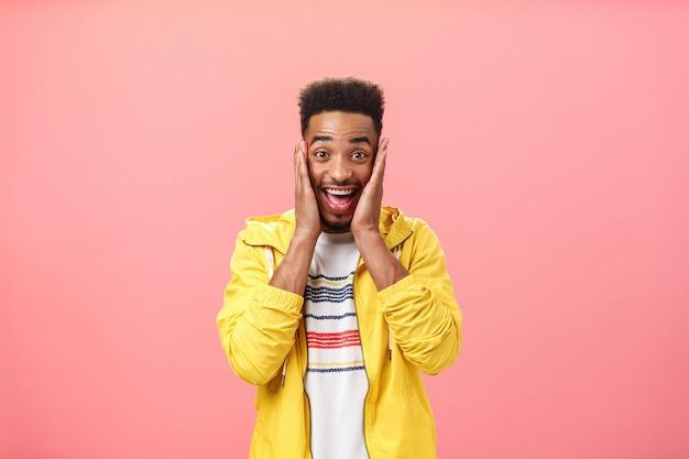 巻き毛のハイで幸せなハンサムなアフリカ系アメリカ人の男子生徒を驚かせた自分の幸せを信じることができません...