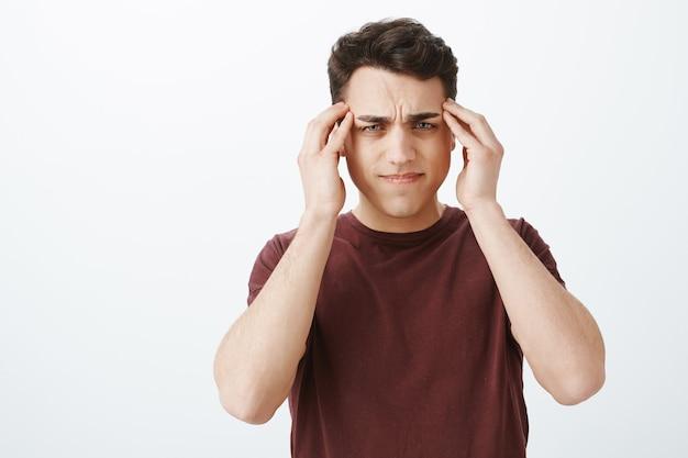 Не может сосредоточиться на работе из-за головной боли. портрет мрачного расфокусированного привлекательного мужчины