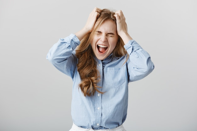Больше не выдерживает давления. напряженная сытая по горло европейская модель в синих воротничках, кричащая или кричащая, держась за голову с закрытыми глазами, чувствуя боль или страдая от депрессии