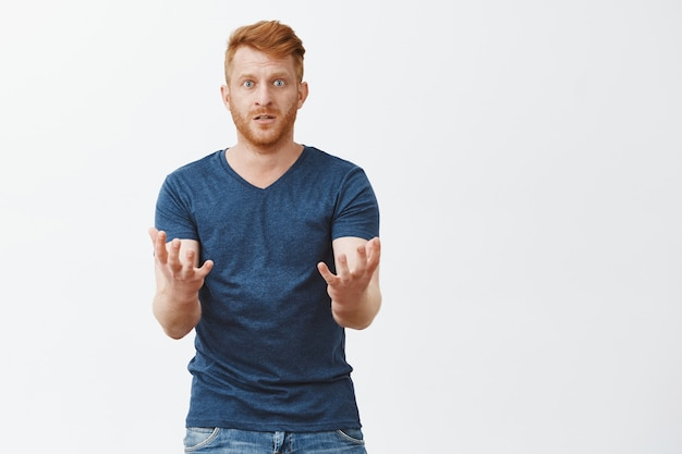 Cannot understand how it happened. portrait of confused upset ginger man in despair with bristle, lifting hands in clueless and unaware gesture, gasping and staring questioned over grey wall
