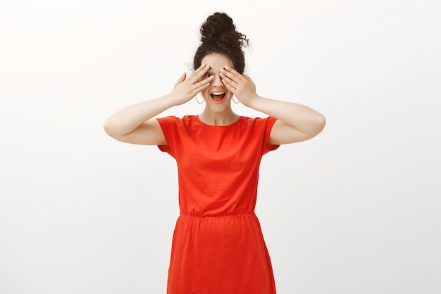 驚きを見るのが待ちきれません。スタイリッシュな赤いドレスを着た肯定的な興奮した女性、ニヤリと手のひらで目を覆い、指から覗く
