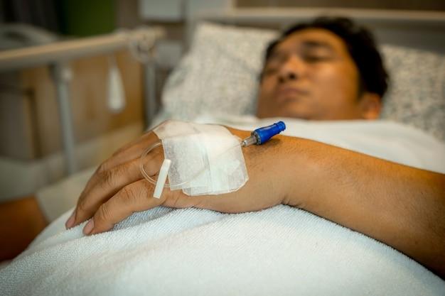 病棟のベッドにある男性患者の手のカニューレ。