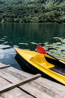 Canoe floating near the wooden pier on lake