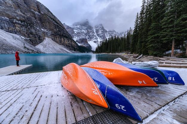 Каноэ припарковано на деревянном пирсе со скалистыми горами в моренном озере в национальном парке банф, канада
