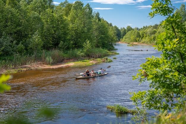 여름날 숲의 강에서 카누 여행. 숲 강에서 카누를 하는 세 남자. 물 표면은 푸른 하늘을 반영합니다. 모험을 하면서 캐나다를 여행하는 관광객들. 자연과 스포츠의 만남
