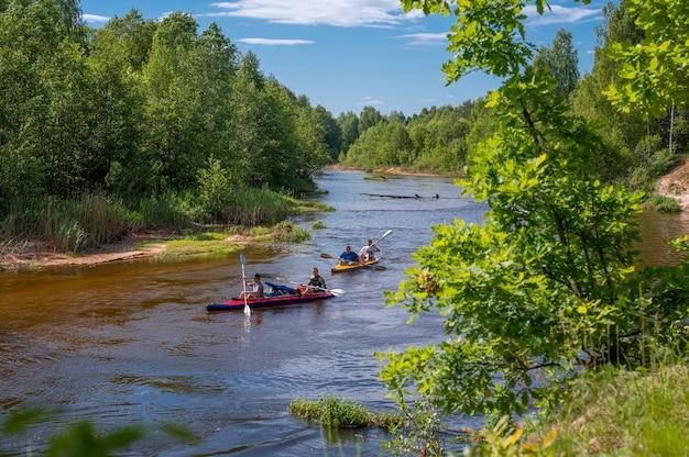 숲 강에서 카누. 숲 강에서 카약으로 운전하는 친구. 여름에는 활동적인 오락과 오락. 여러 사람들이 멋진 주변 환경과 함께 잔잔한 물에서 래프팅을 하는 풍선 카누를 팀으로 구성합니다.