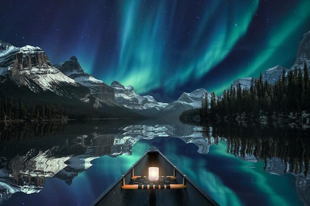 カナダ、ジャスパー国立公園のマリン湖の山脈をオーロラと一緒にカヌーで走る。ファインアートのコンセプト