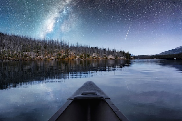 Canoeing with milky way and shooting star reflection on maligne lake at jasper national park