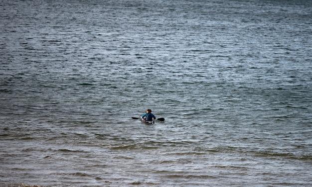 Каноист занимается спортом на пляже