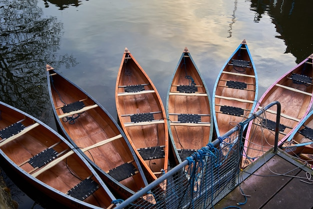 Canoes on the river near a jetty in a park under the sunlight