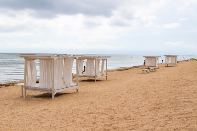 Навесы с белыми занавесками на песчаном пляже у моря. серые облака.