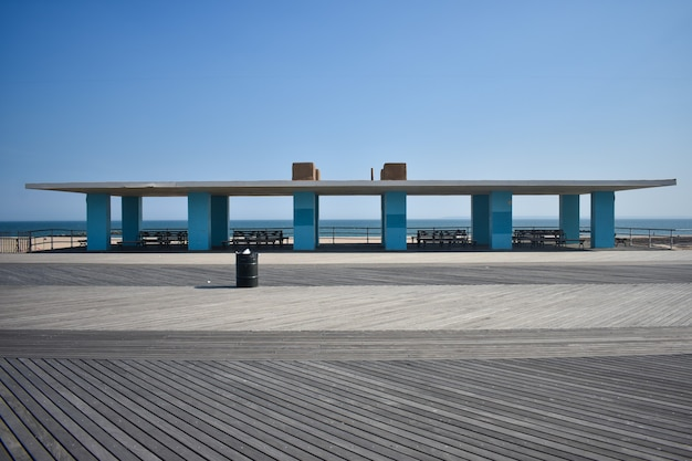 Canopy building at the beach with blue columns, white roof and benches