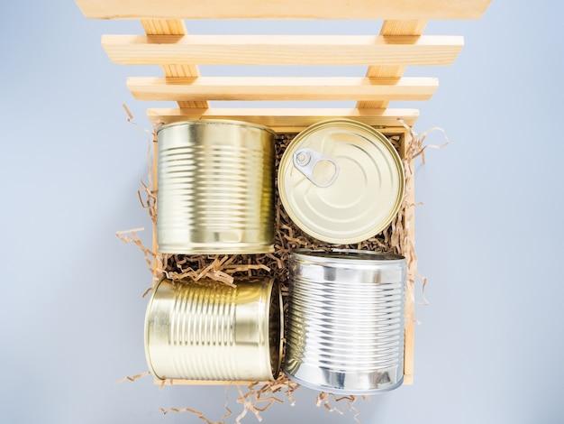캔은 부드러운 뒷면이있는 나무 상자에 포장되어 회색 배경, 클로즈업, 모형에 격리됩니다. 격리 중 음식이나 선물의 개념. 음식 기부, 음식 배달 상자.