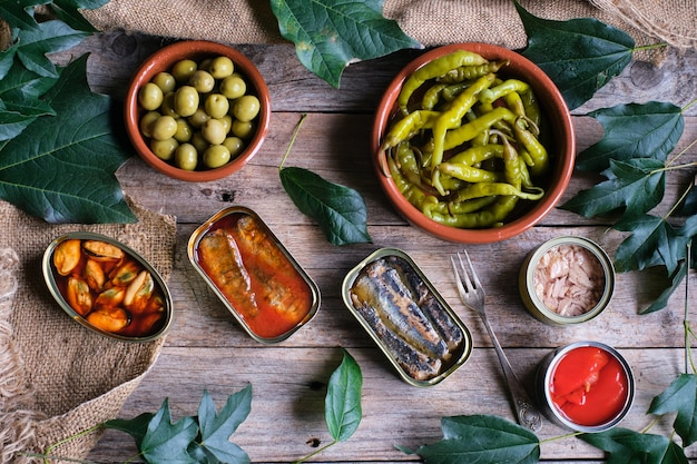 Cans of assorted preserves with olives and chillies viewed from above on rustic wooden table
