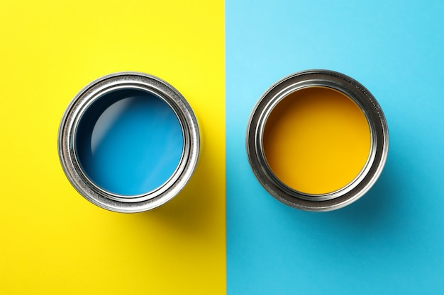 Cans of blue and yellow paint on two tone surface