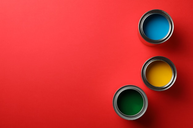 Cans of different paints on red surface