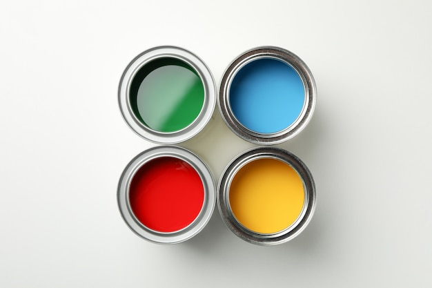 Cans of different paints on white surface
