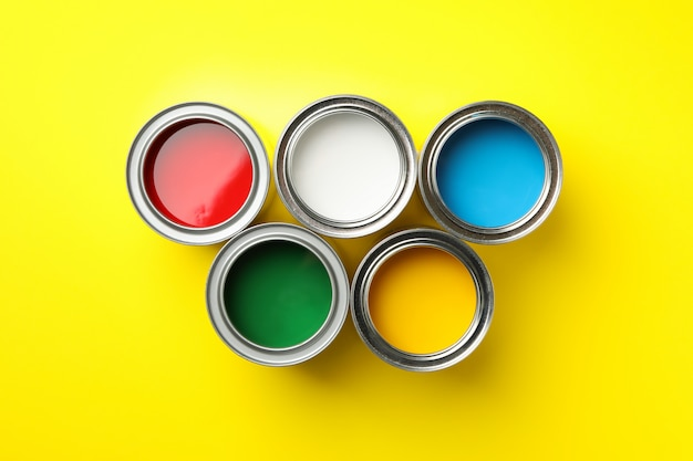Cans of different paints on yellow surface