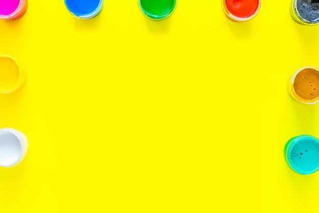 色とりどりのペンキの缶は、黄色の背景の写真の側面と上部にあります...