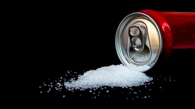 Банки сладких напитков разливаются отдельно на черном фоне, концепция сравнения содержания сахара в освежающих напитках.