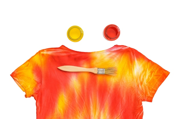 Cans of paint, brush and t-shirt in tie dye style isolated on white surface