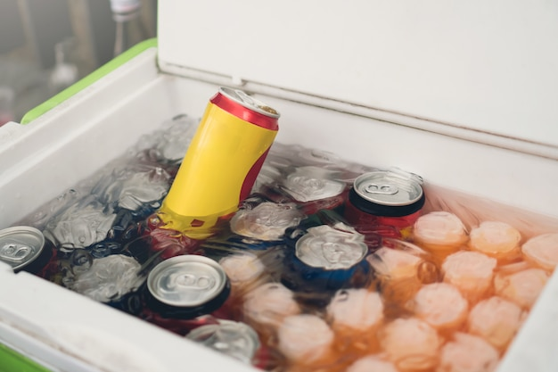 Cans of soft drinks in an ice box.