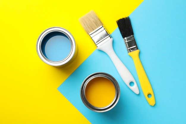 Cans with paint and brushes on two tone background, top view