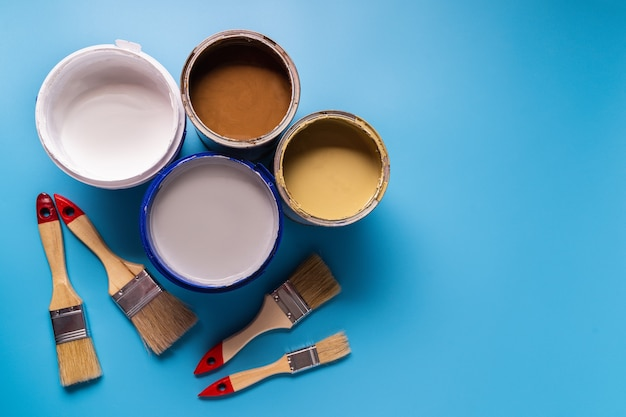 Cans with paint of different colors and paint brushes