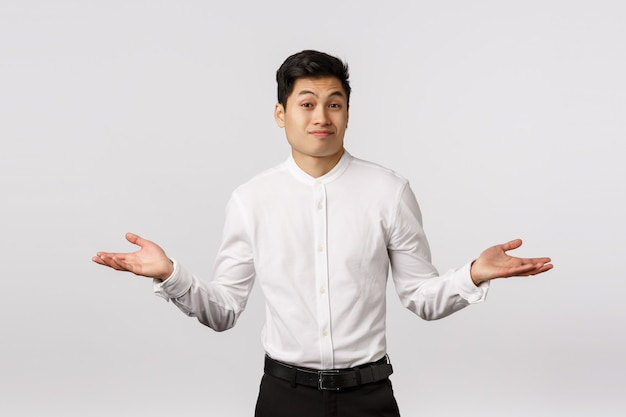 Cant help you sorry. handsome asian businessman shrugging, spread hands sideways dismay and wonder, frowning and smirk awkward, dont know anything, clueless, unable to answer