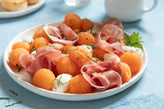 Салат из дыни с канталупой, моцареллой и ветчиной прошутто