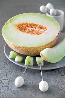 Дыня канталупа нарезанная на серую тарелку с фруктовыми вилками