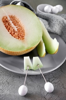 Cantaloupe melone sliced on grey plate