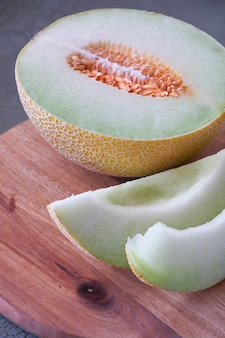 Cantaloupe melone sliced on wooden board on dark