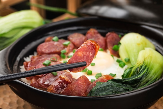 Cantonese style cooking of claypot rice with waxed meats