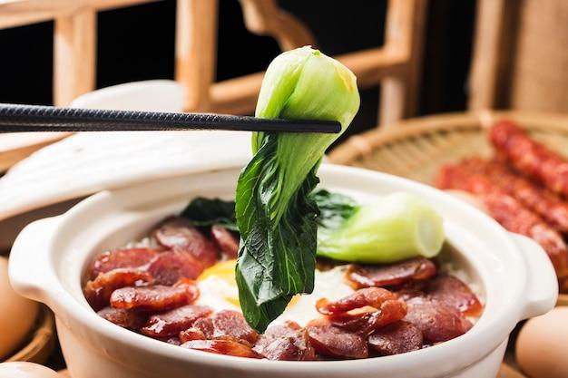Приготовление риса в глиняном горшке с вощеным мясом по-кантонски