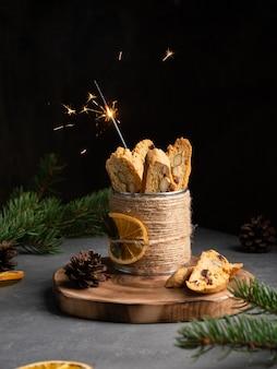 オレンジの皮、アーモンドナッツ、木製デッキ、まな板の上の乾燥クランベリーとcantucci(イタリアの二重焼きクッキー、ビスコッティ)。暗い背景。