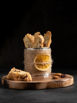 Cantucci (italian double baked cookies, biscotti) with orange zest, almond nuts and dried cranberry on wooden deck, cutting board. dark background.