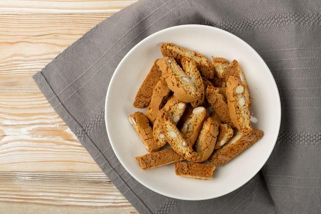 素朴なテーブルクロスの黄麻布の背景にビスコッティディプラート。伝統的なイタリアのカントチーニナッツクッキー。白いプレートの上面にアーモンドと自家製cantucciショートブレッド