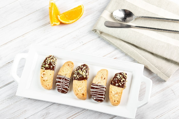 Cantuccini biscuits. italian biscotti cookie on white plate on a white wooden background. top view.