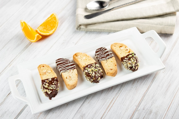 Cantuccini biscuits. italian biscotti cookie on white plate on a white wooden background.
