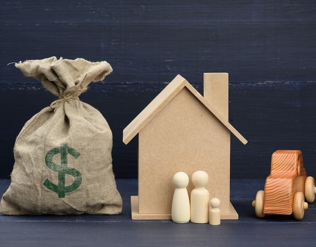 Canvas bag full of money and a wooden house. concept of buying real estate, renting out.