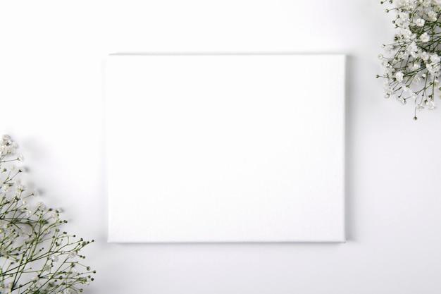 흰색 배경에 작은 흰색 꽃과 캔버스 모형.