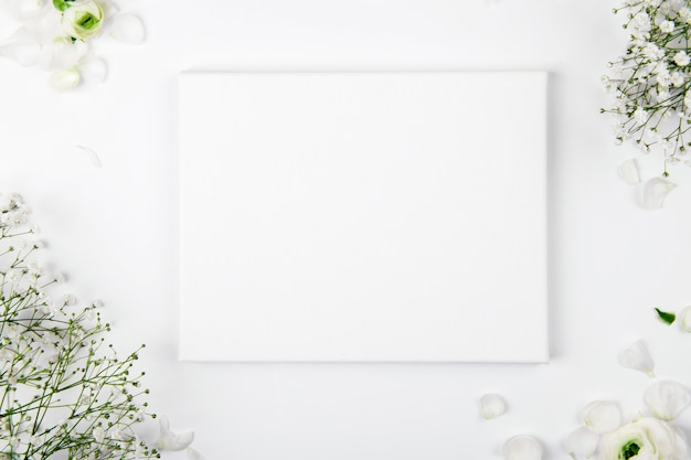 Canvas mockup with smal white flowers on a white background.