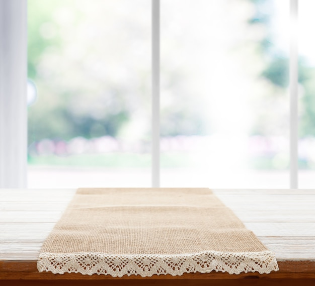Салфетка холстины с кружевом, скатерть на перспективе деревянного стола. летний пейзаж за окном.