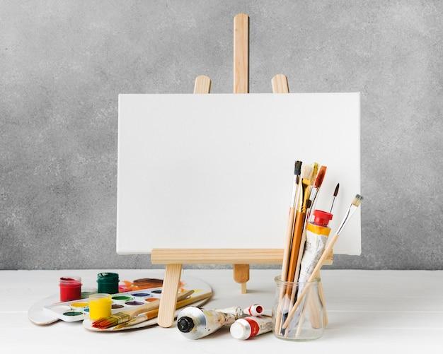 キャンバスにイーゼルと水彩絵の具の正面図